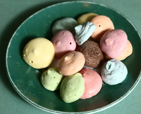 kiss biscuits: meringue kiss pastry macaron cookies on the green plate close up photo