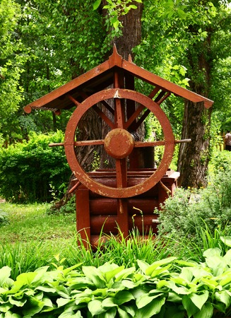 well made: old wooden well with bin and steering weel in country museum estate Stock Photo
