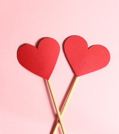 wooden stick: two red paper heart on wooden stick together on the pink background and copy space for valentines day congratulation description