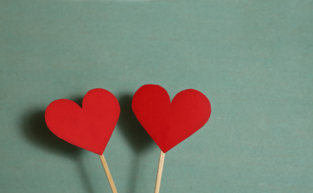 wooden stick: two red paper heart on wooden stick together on the blue background and copy space for valentines day congratulation description