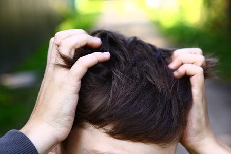piojos: apuesto muchacho preadolescente rascarse la cabeza picor debido a la invasi�n de piojos