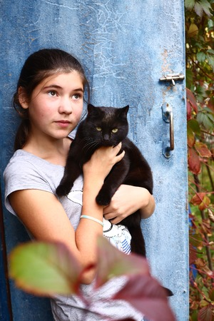 teen pretty girl wit black cat on the shabby door background Reklamní fotografie