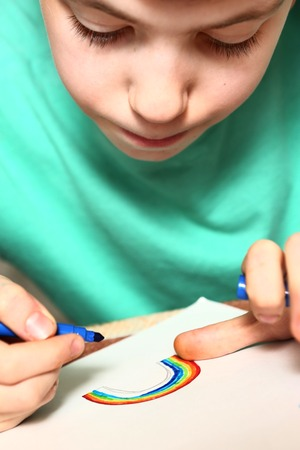 boy drawing rainbow at art school lesson Stock Photo