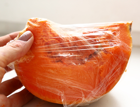 de hand verpakken stuk gesneden pompoen in voedsel film op te slaan in de koelkast Stockfoto