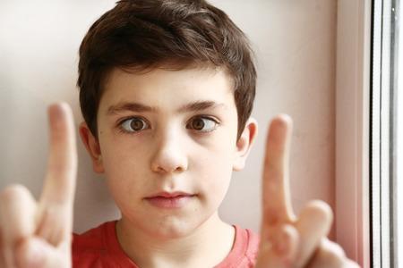 предподростковый красивый мальчик играть косоглазие трюк с его глаз и пальцев крупным планом портрет