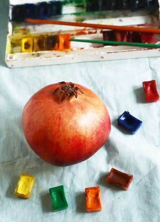 artistry: ripe red pomegranate with art aquarell paints and brushes still life on blue cloth