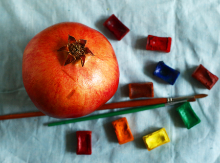 aquarell: ripe red pomegranate with art aquarell paints and brushes still life on blue cloth
