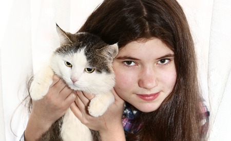teenager pretty girl with long dark brown thick hairs hold cat close up portrait isolated on white Stock Photo