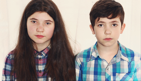 scottish female: siblings preteen boy and teenager girl with long thick brown hair brother and sister close up portrait isolated on white Stock Photo