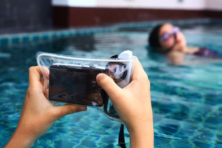 pool preteen: hands hold camera in protective slipcover covering ready to make underwater shoot pictures footage of synchronized swimmer girl