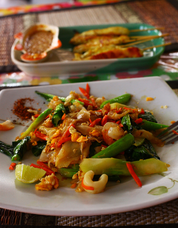 notional: thai spicy noodle with vegetables and sea food and chicken barbecue served in the street cafe