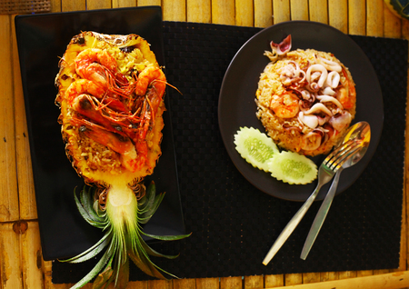 notional: hai food restaurant stuffed with rise shrimps prawn raisin fruit pineapple and seafood octopus squid rice close up photo on the table Stock Photo