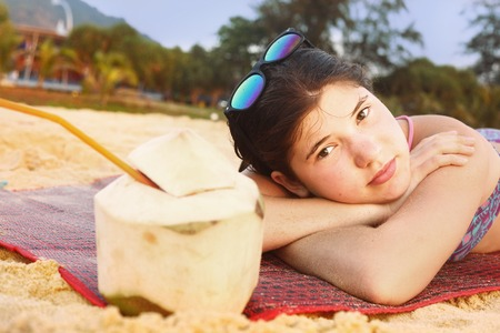 water hottub: teenager girl with coconut and straw lay on the beach close up portrait Stock Photo