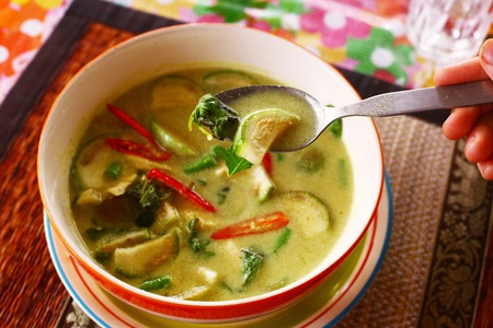 chilly: green curry thai soup with sea food coconut milk cream and red hot chilly pepper spicy in bowl with spoon Stock Photo