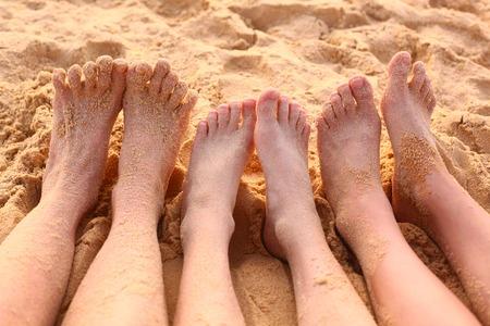 sandy feet: bare feet on the sandy beach close up photo