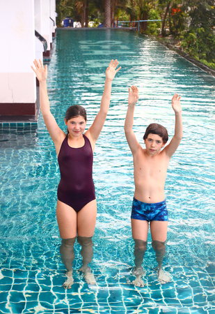 pool preteen: pretty swimmer teenager girl and preteen boy jump exercise in swimming pool water