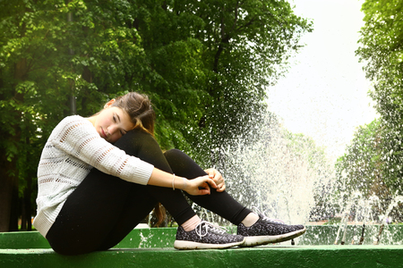 dark brown hair: lonely teen girl with long dark brown hair in the park on fountain background close up photo Stock Photo