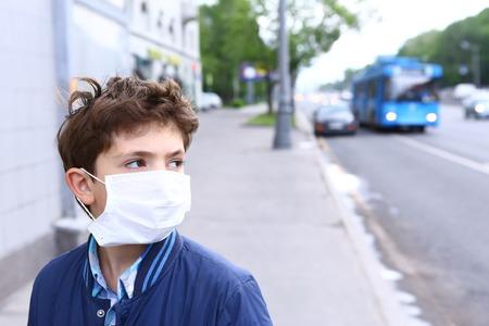 Apuesto muchacho preadolescente en la máscara protectora en el fondo urbano Foto de archivo - 59002423