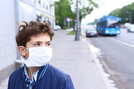 preteen handsome boy in protective mask on the urban background 版權商用圖片