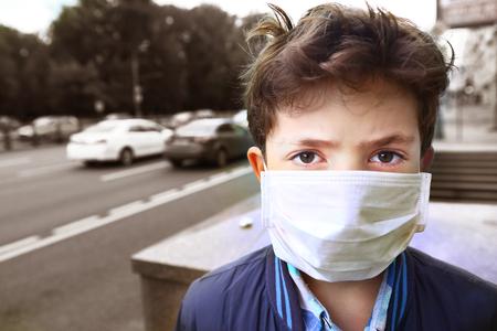 preteen knappe jongen in beschermend masker op de stedelijke achtergrond Stockfoto