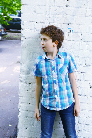 seek: preteen handsome boy close up photo hiding around the corner play hide and seek game