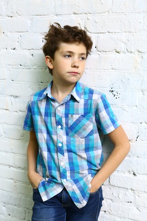 cotton fabric: preteen handsome boy in checked blue shirt close up portrait on white brick wall background