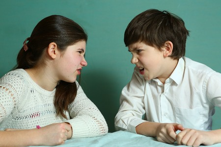 difficult period: siblings brother and sister quarreling teasing each other close up portrait
