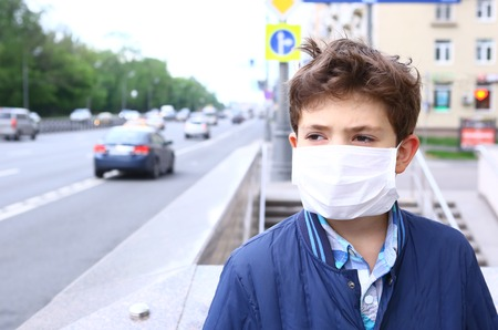 ecological problem: preteen handsome boy in protective mask on the urban background Stock Photo