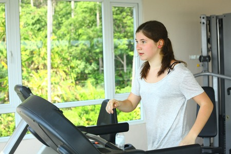 pony tail: teen pretty girl with pony tail jogging on treadmill close up portrait