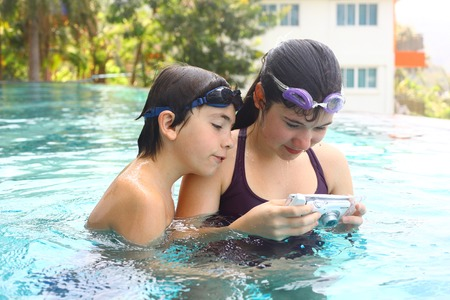 pool water: teen siblings brother and sister take photos with underwater cover camera close up portrait in open air thai swimming pool Stock Photo