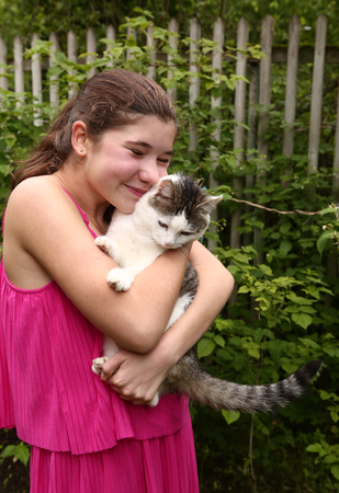 close your eyes: een pretty girl in pink dress hug siberian cat close up photo on green garden fence country summer background Stock Photo