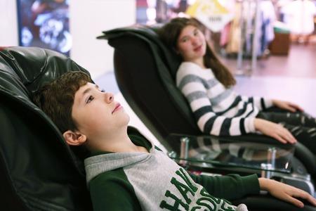 masajes relajacion: adolescente Hermanos hermano y hermana en silla de masaje en el centro comercial