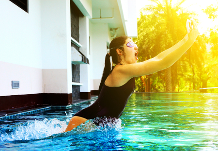 pool preteen: teenager girl in swimming suit jump in water in swimming pool with camera in protective waterproof slipcover cover for underwater photo shooting footage Stock Photo