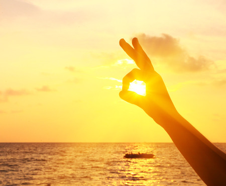 human hand show hair face with fingers and sun eye on the sunset background