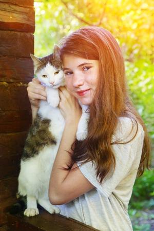 pubertad: adolescente de niña bonita con el gato de cerca retrato en el fondo de verano país