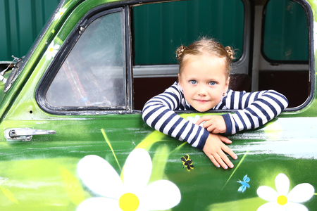 blond smiling preteen girl in old painted with fowers car cose up portrait