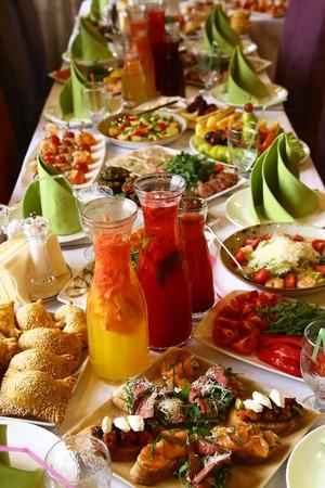 Restaurante mesa larga servida con comida de aperitivo y bebida para el partido Foto de archivo - 62035512