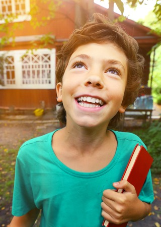 country happy boy close up portrait with book laughing on the cottage house background