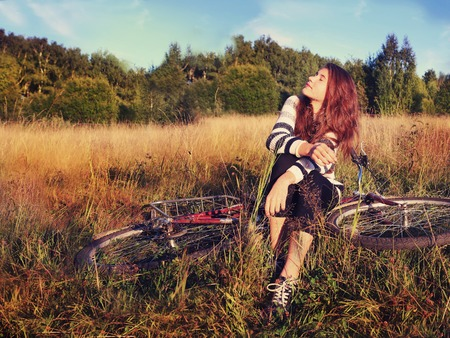 dark brown hair: teen pretty girl with long dark brown hair sit on bicycle in the summer sunny field have break sunbathing face close up portrait