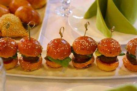 sliders: mini hamburger with salad leaf served on the plate on restaurant table