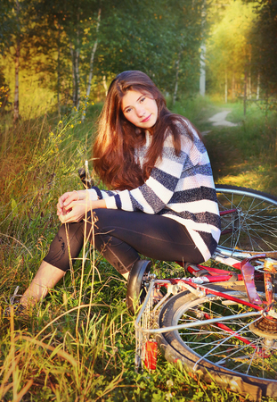 loose hair: teenager girl with long brown loose hair sit on bicycle close up photo on sunny summer forest background