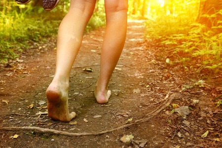 森林のパスに沿って歩く素足をクローズ アップ写真