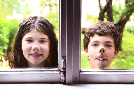 nose close up: teen girl and boy siblings with nose pressed against the window close up portrait Stock Photo