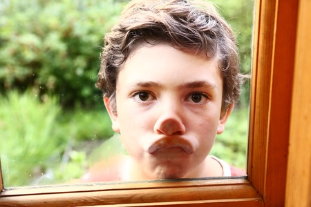 preteen handsome grimacing boy press his nose and mouth against window glass close up portrait on the summer garden background