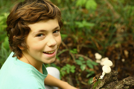 giant mushroom: preteen handsome boy close up photo in the forest with puffball mushrooms Stock Photo