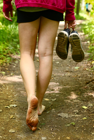 bare feet walking along the forest path close up photo Stock Photo
