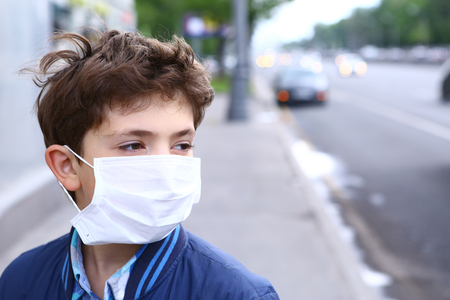 smog: preteen boy in protection mask on the highway city background Stock Photo