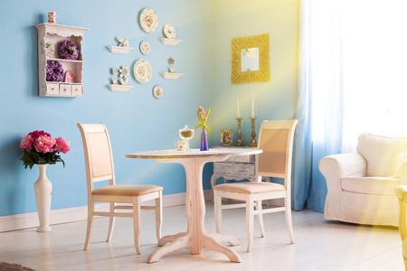 Blauwe eetkamer met decoratie borden en frame op de muur vaas