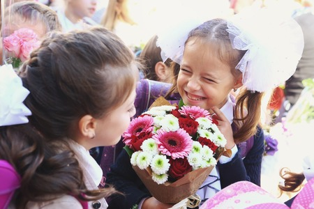 beginning school year: Moscow, Russia - September 1, 2016: Unidentified girls with flowers bouquet on solemn meeting of first grade kids, called the Day of Knowledge, signify the beginning of school year. Editorial