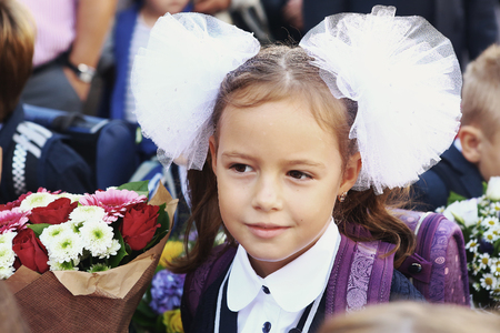 signify: Moscow, Russia - September 1, 2016: Unidentified girls with flowers bouquet on solemn meeting of first grade kids, called the Day of Knowledge, signify the beginning of school year. Editorial